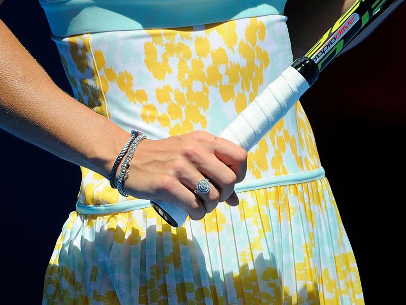 Caroline Wozniacki wears a diamond tennis bracelet design while holding a racquet