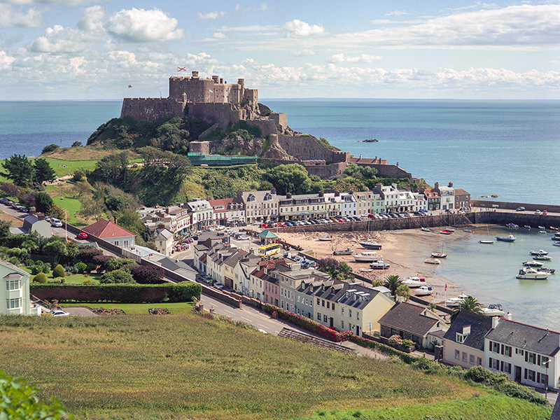 A view of Gorey Castle, pastel houses, and the harbor in Jersey Channel Island