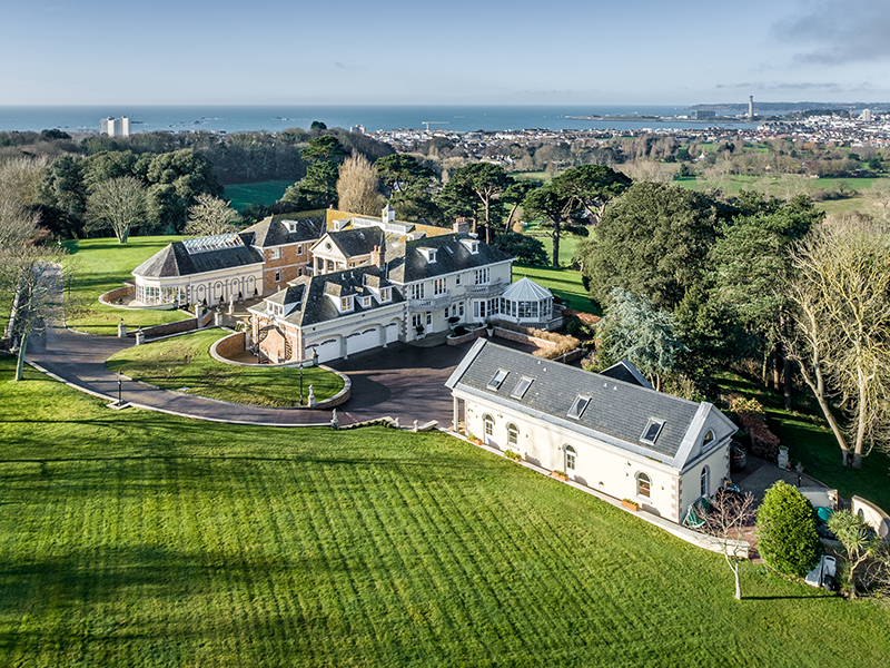 Aerial view of a large countryside mansion with ocean in distance