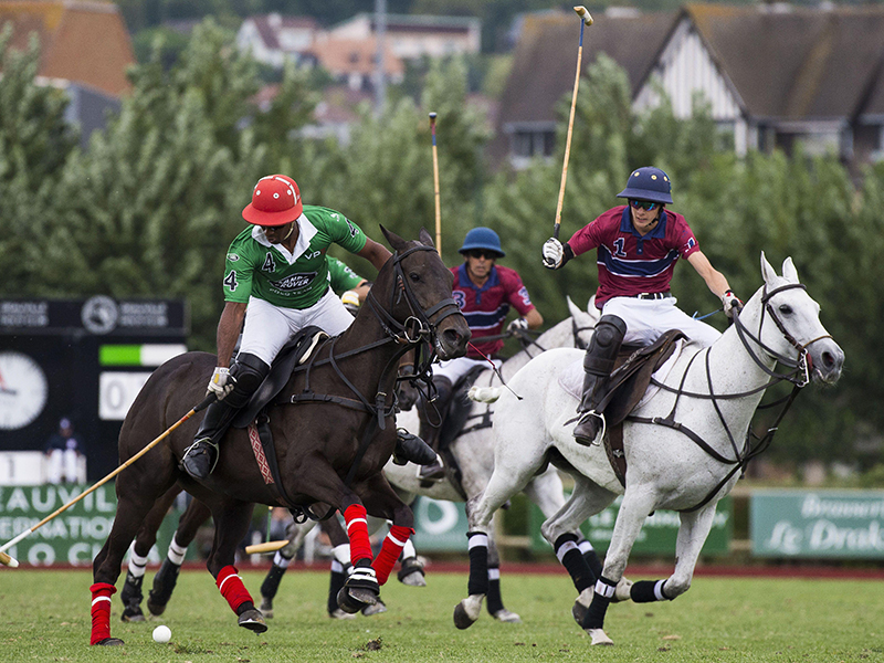 Three polo players mid-match on a field
