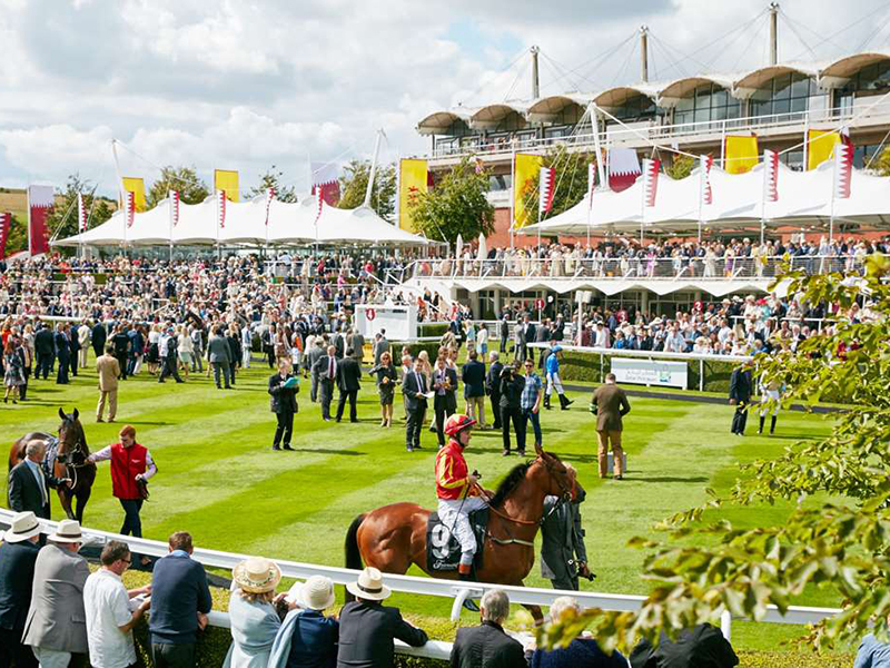 A crowd looks on as horses and jockeys pass by at the Qatar Goodwood Festival