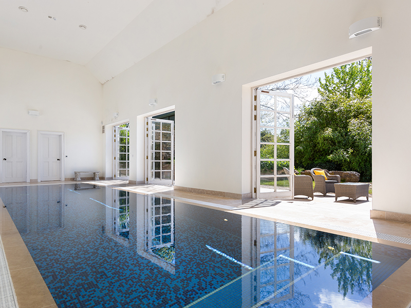 An indoor swimming pool with large doors leading to a terrace