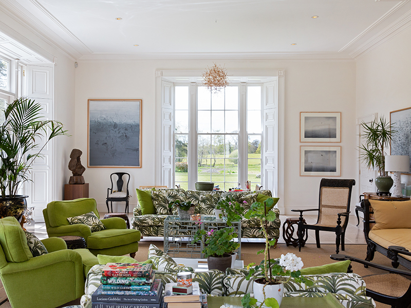 Green and white furniture with many large plants in the orangery