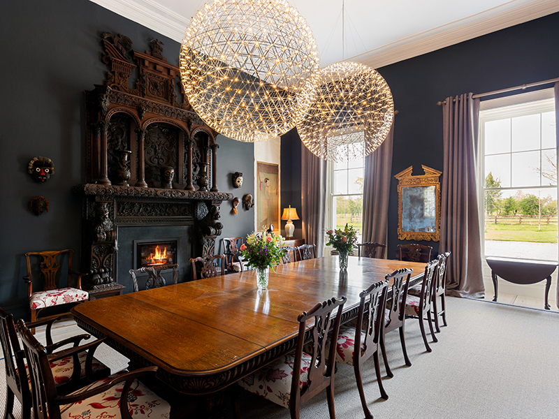 A formal dining room with large round modern light fixtures