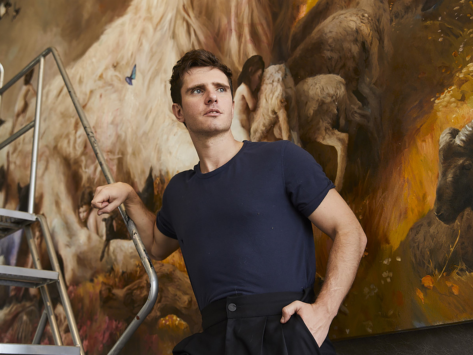 Portrait of Guillermo Lorca in front of a large scale oil painting