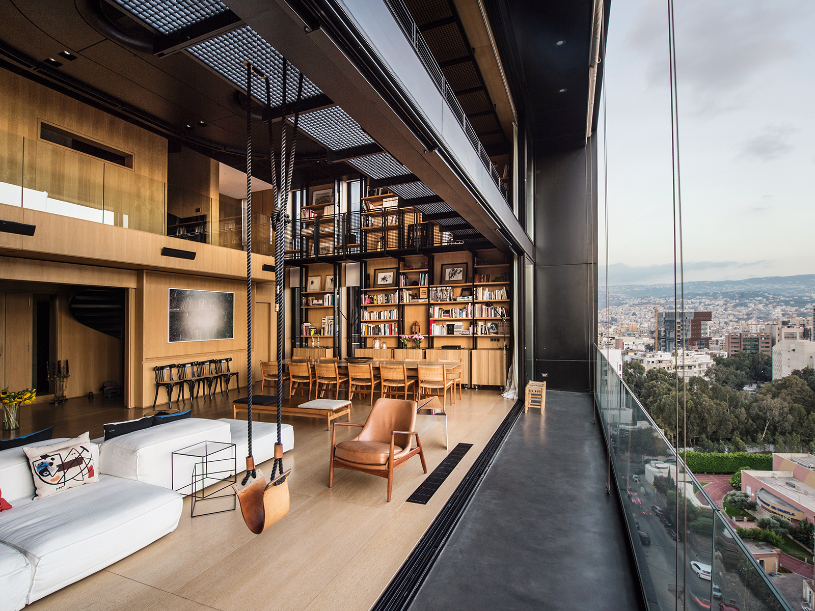 A loft apartment with sweeping glass windows and views onto a city