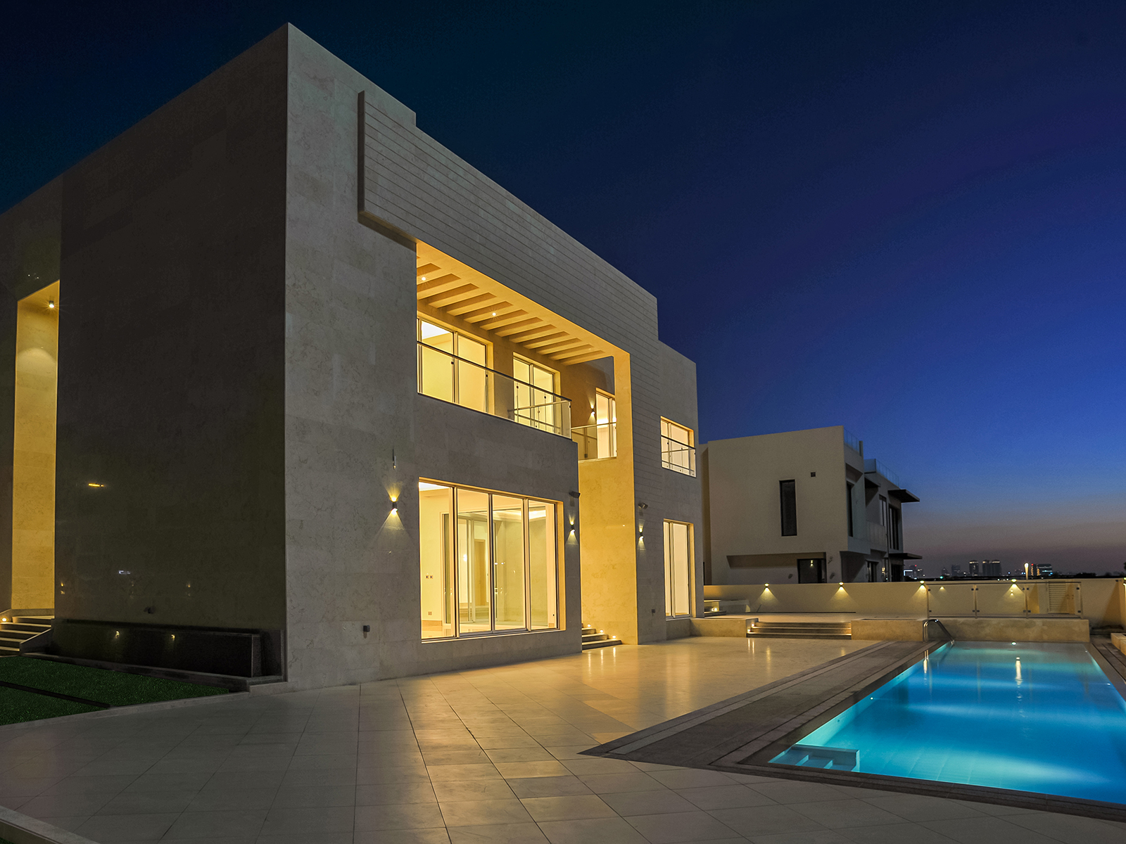 The outside view of a villa and pool at night