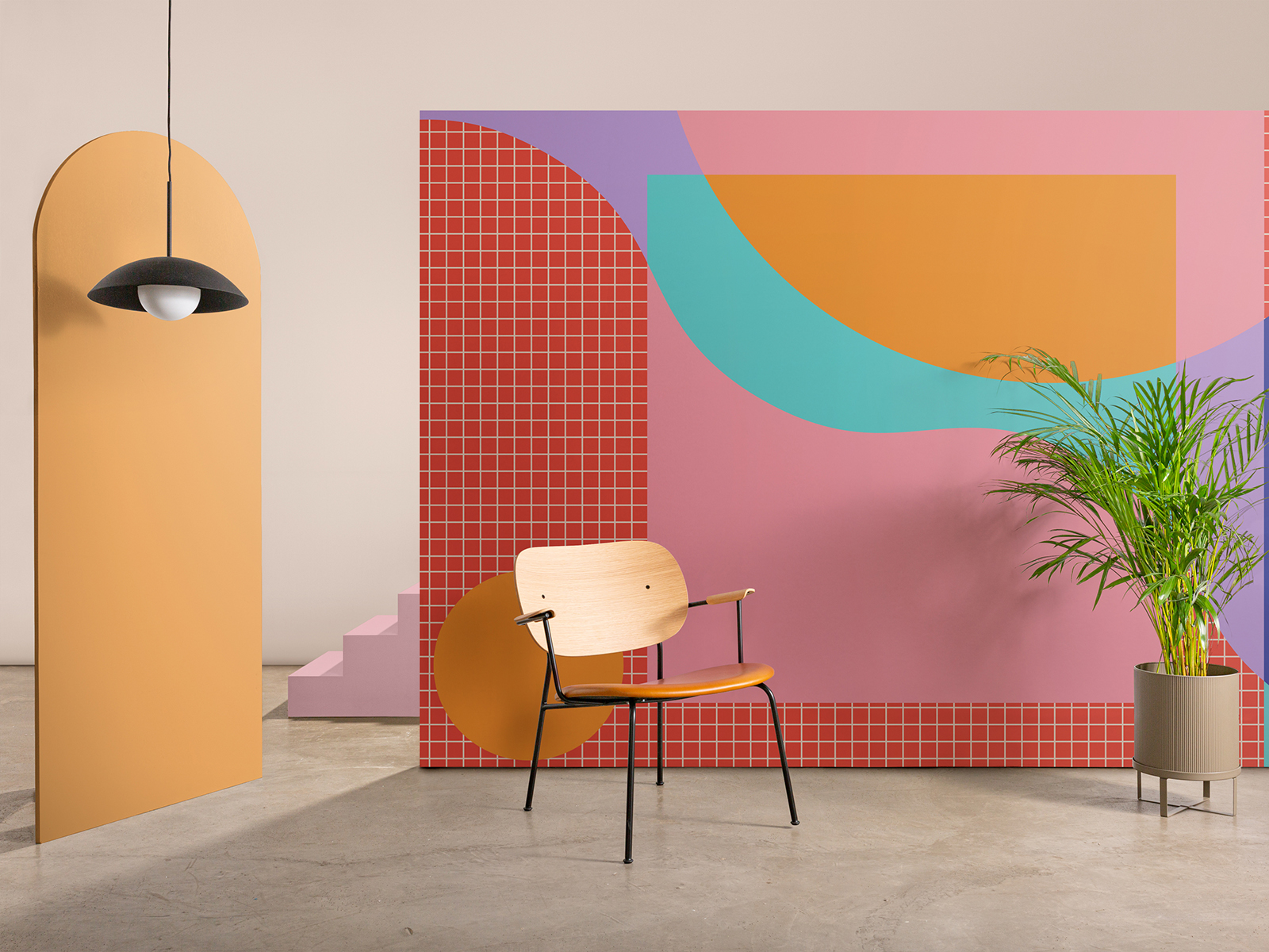 A geometric wallpaper design on a freestanding wall with a armchair and plant