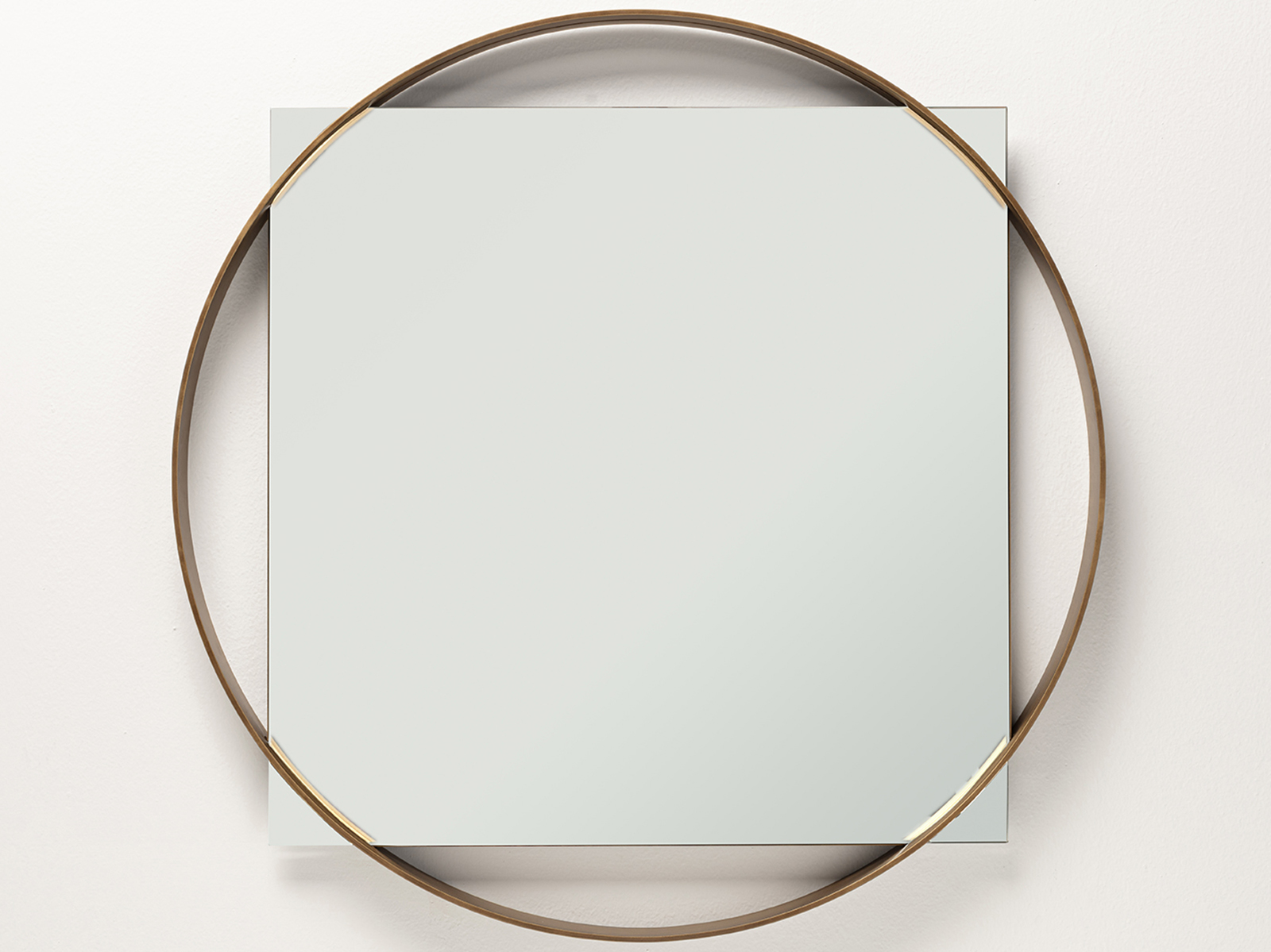 A round gold frame with a square mirror contained inside