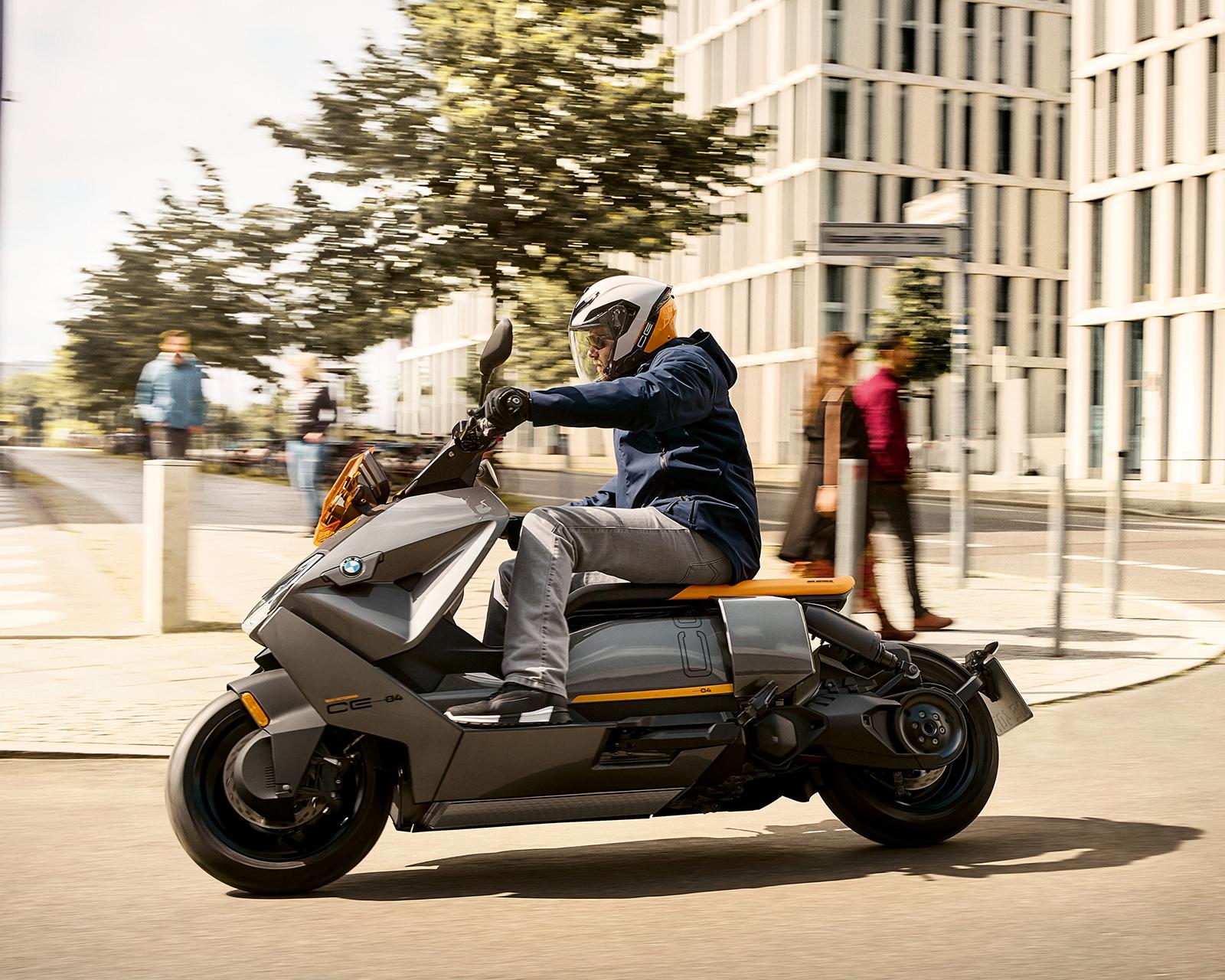 A man rides the BMW CE 04 on a city street