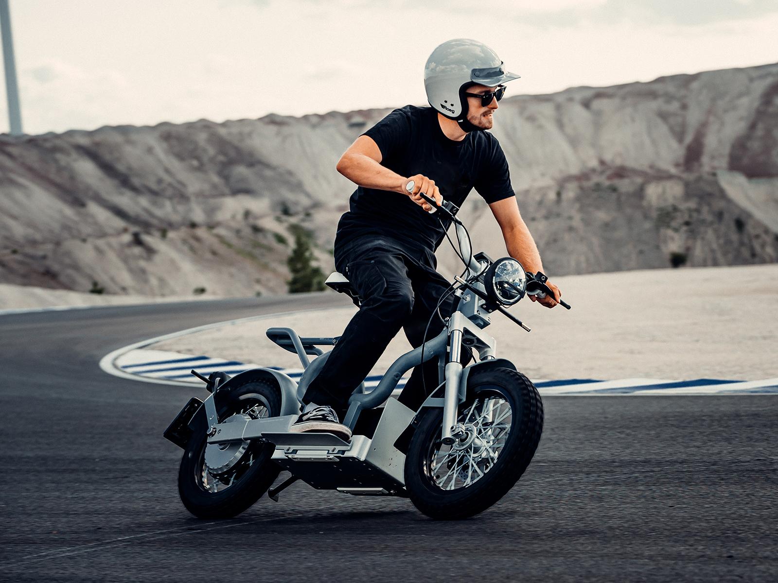 A man rides a Cake Makka moped along a race track