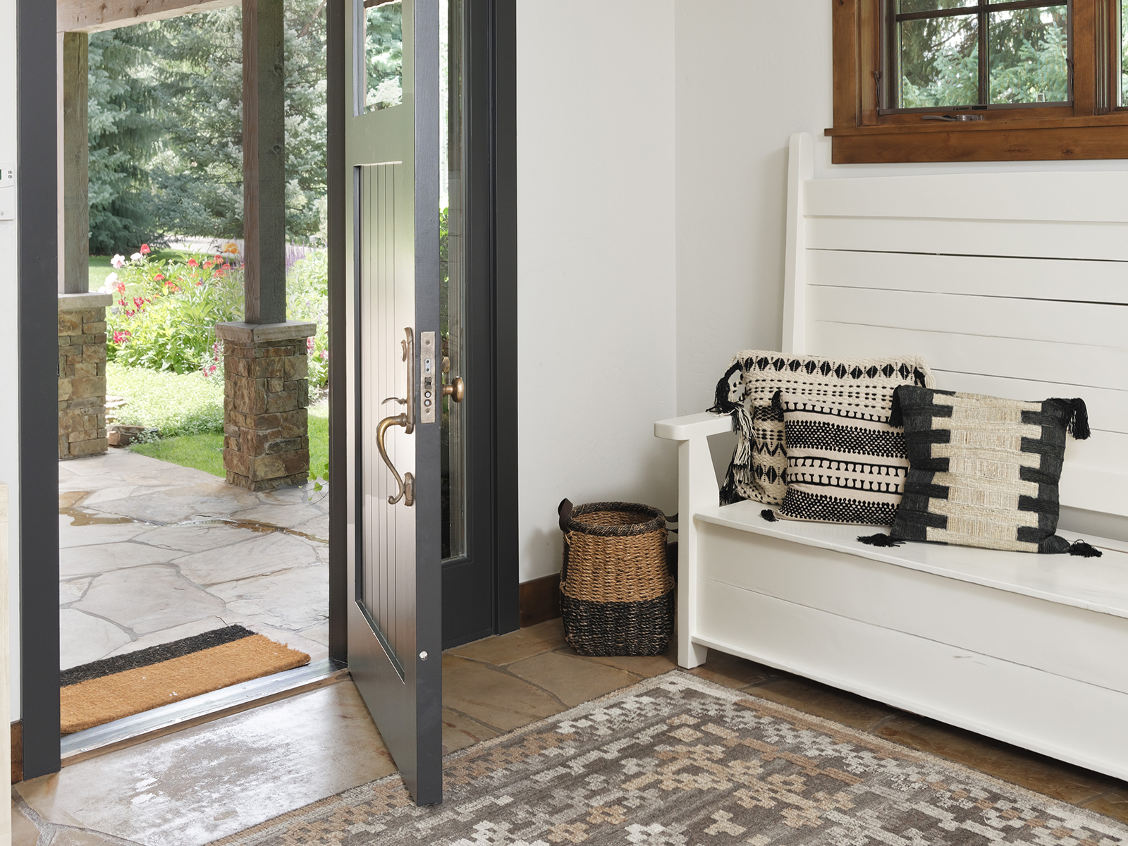 An entrance hall with wooden furniture and an earth-toned rug