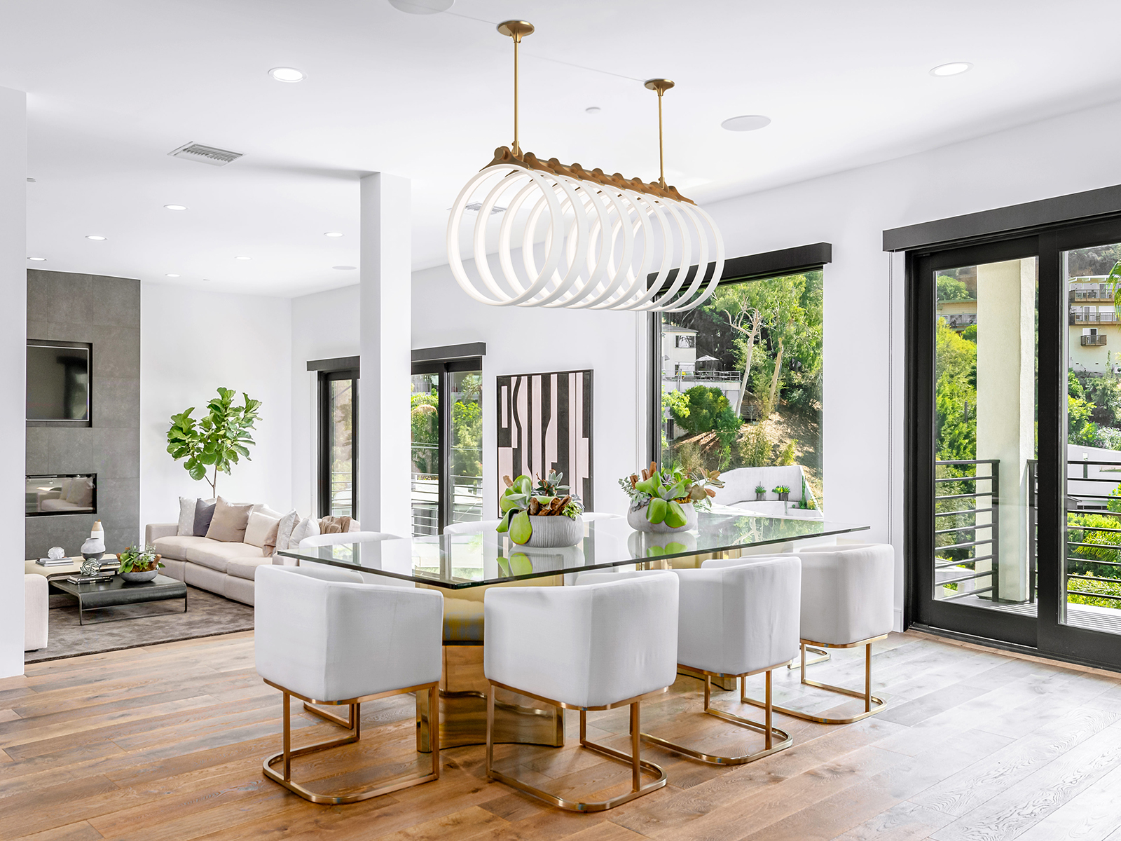 The rings of a Samsara chandelier hang over a modern dining table