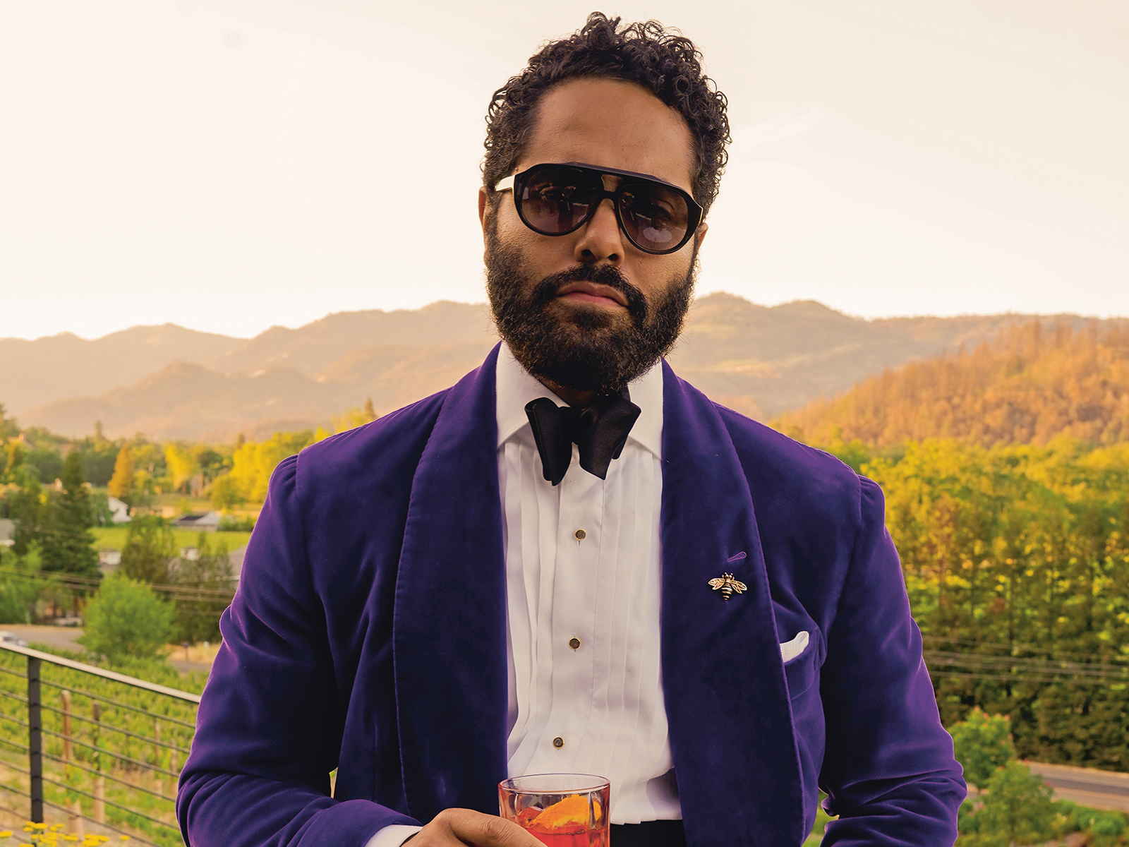 Angel Ramos stands in front of vineyards in a blue velvet suit jacket