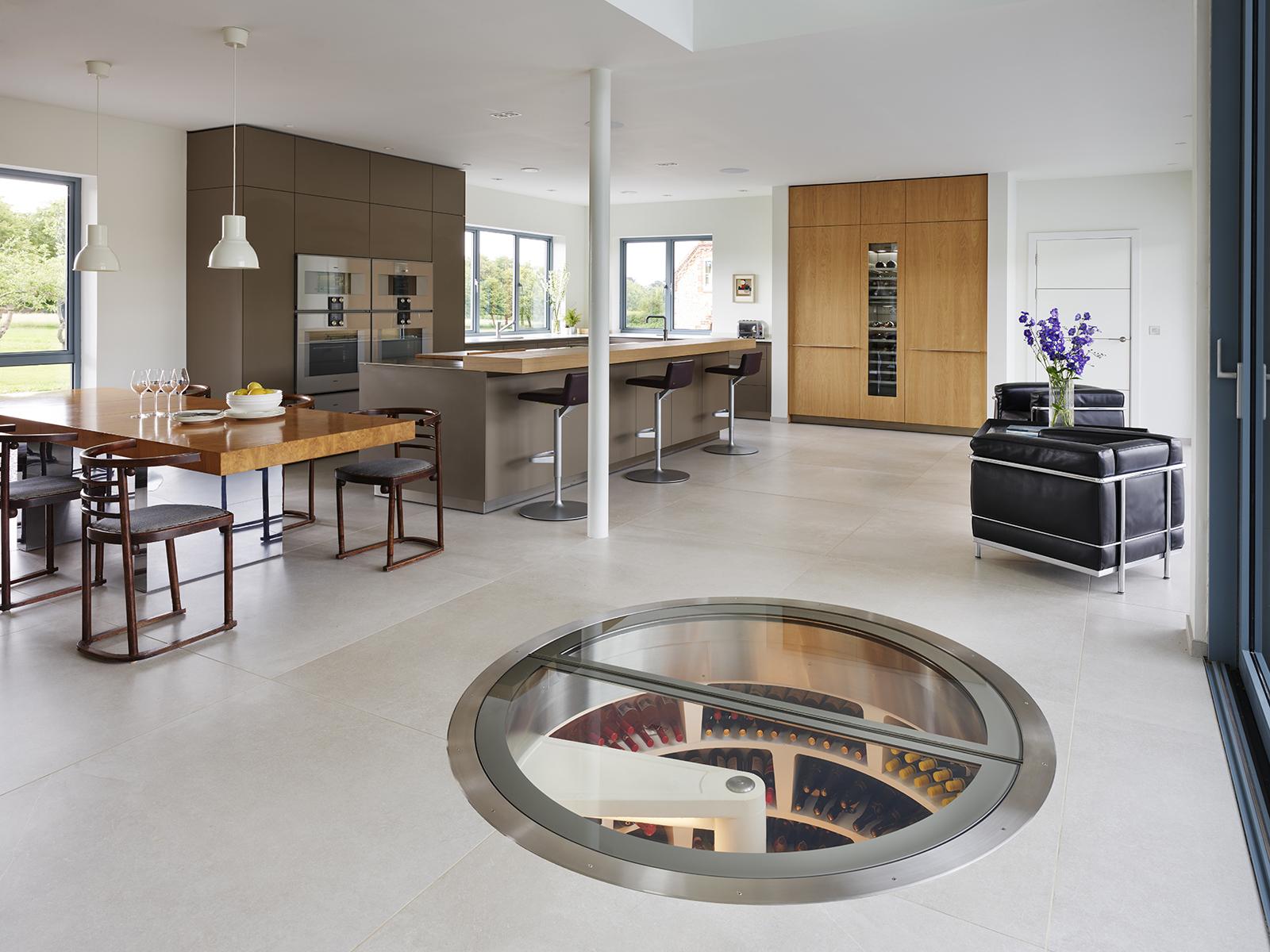 A kitchen with view into a circular spiral underground cellar