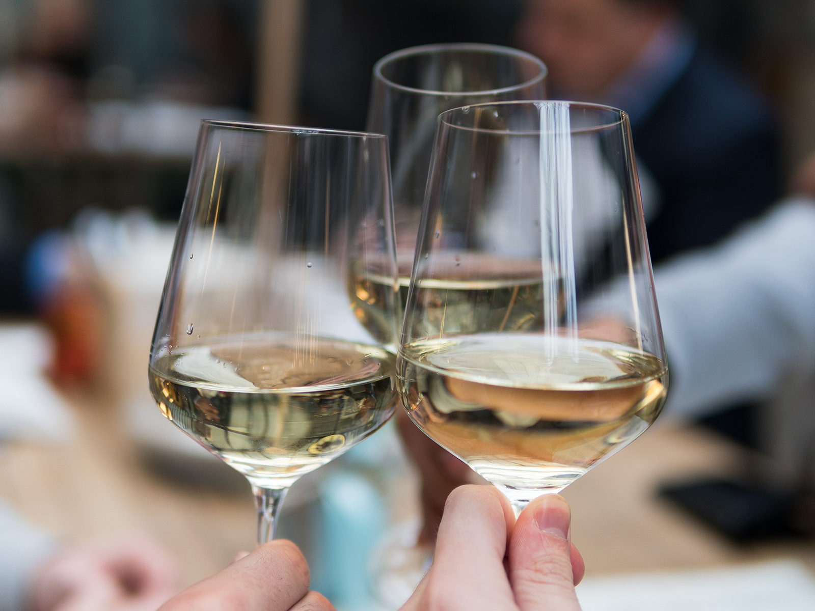 Three white wine glasses being clinked together