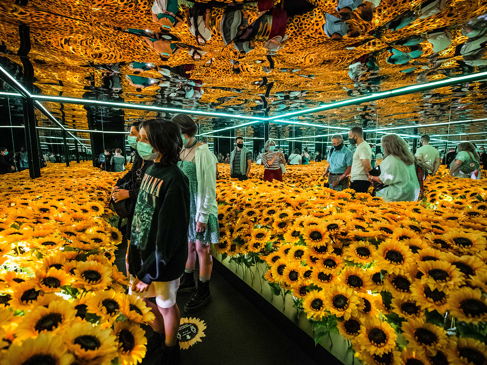 Visitors walk through a mirrored room filled with sunflowers