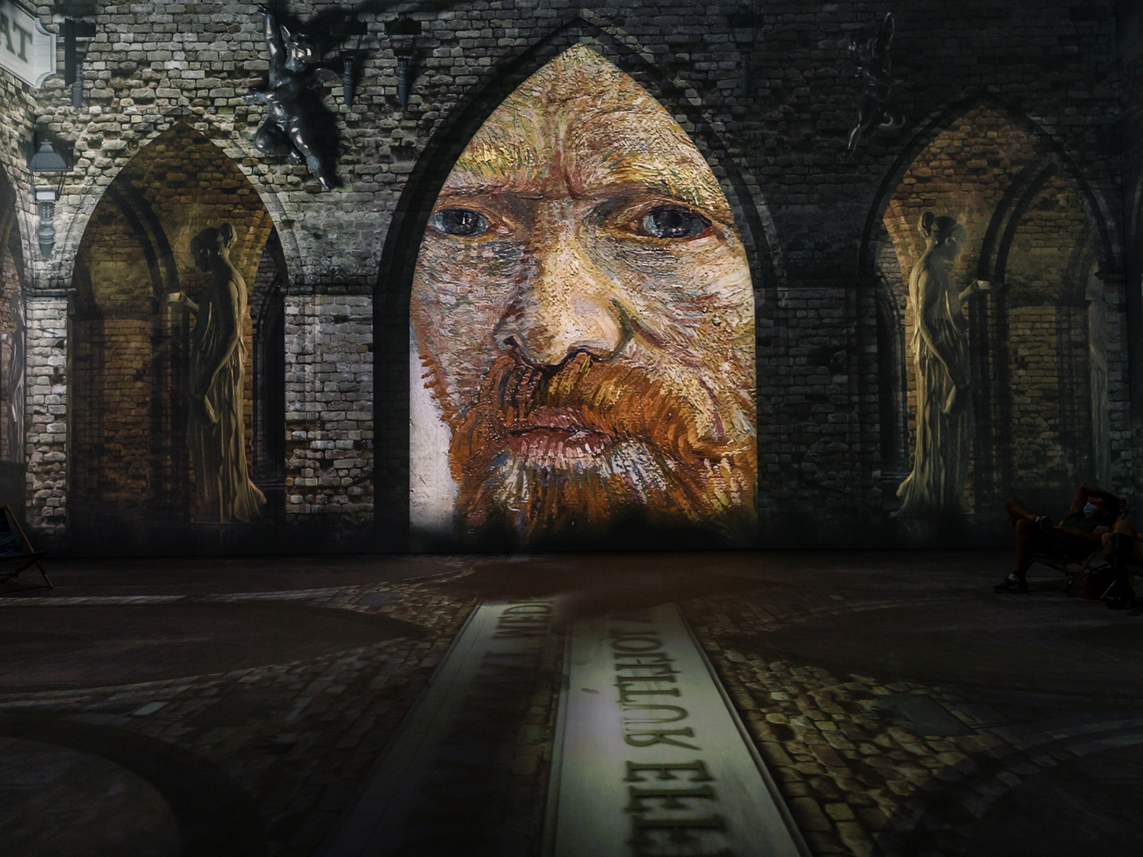 A portrait of Van Gogh projected onto an arched wall